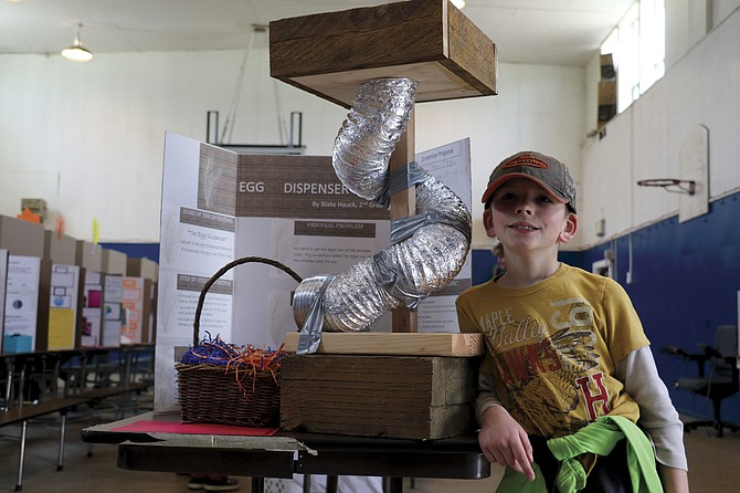 Kings Valley Charter School second grader Blake Hauck shows off the Egg Dispenser at the Invention Convention on Thursday afternoon.