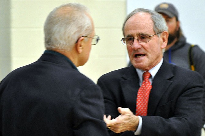 Senator Jim Risch (right) talks with an unidentified man prior to the Nov. 24 public meeting on the Lochsa land exchange.