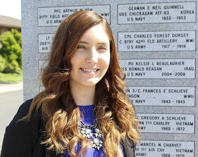 Lauren Beeman, 17, stands in front of one of the granite walls at the Jerry Taylor Veterans Memorial Plaza. She said her two great-grandfathers served in the military, making the plaza a special place for her.