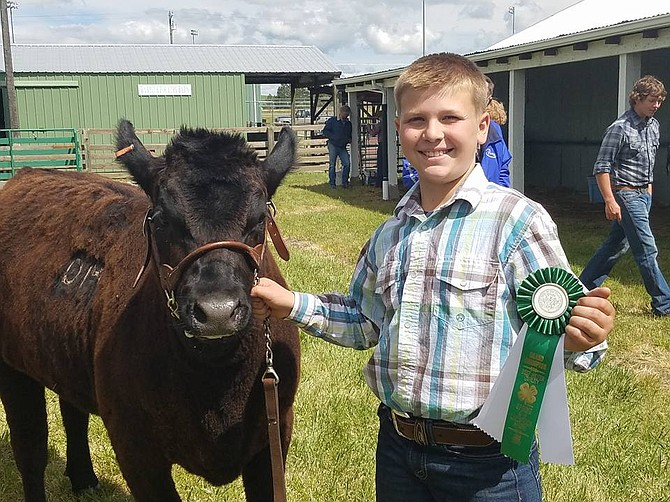 Contributed photo Owen McIntire of the Greencreek Active Workers 4-H Club is seen here with his Grand Champion Quality Breeding Beef project.