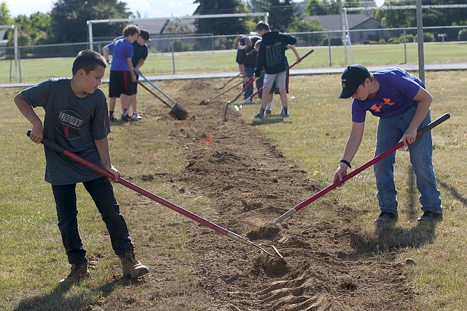 Volunteers both young and old helped install the new irrigation system at the LaCreole Middle School football field on Saturday morning.