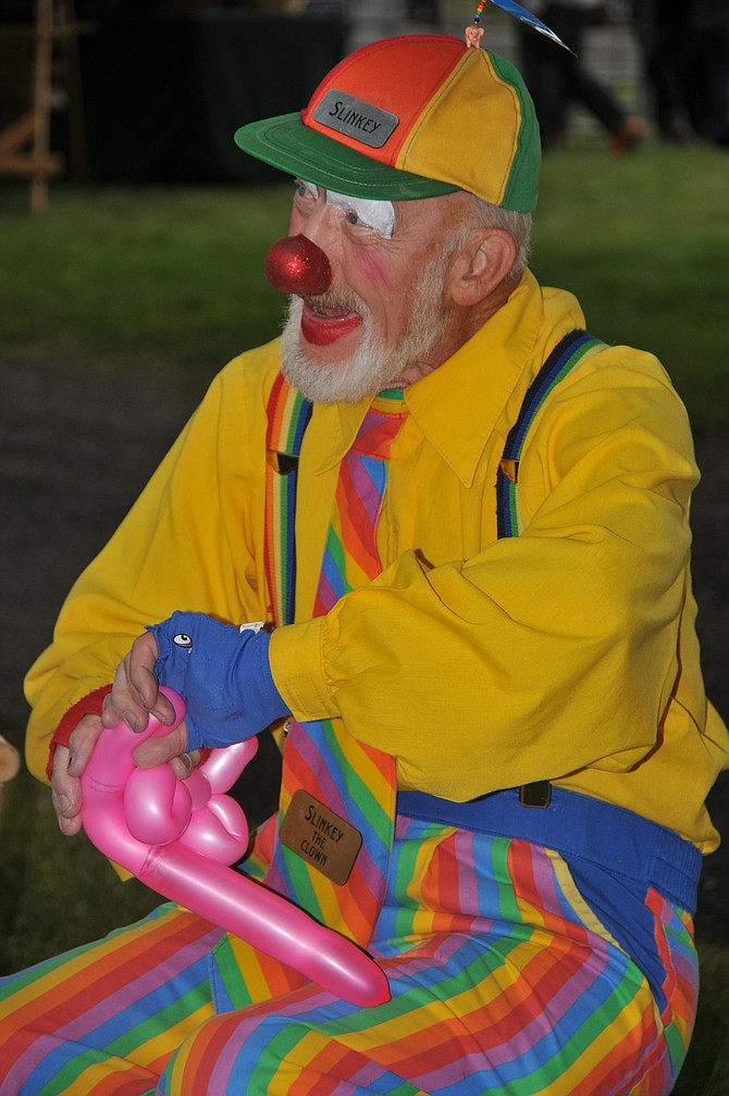 Slinky the Clown interacts with visitors as he produces a balloon animal. Slinky entertained guests at the carnival section of the Raspberry Festival at the Monastery of St. Gertrude on Aug. 8.