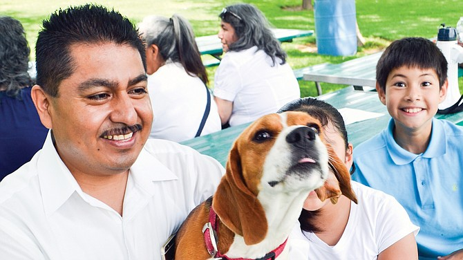 Jorge Huerta and daughter Karen, partially obscured, enjoy a moment in the shade Saturday with their basset hound, Shiloh, at Sunnyside's Central Park.