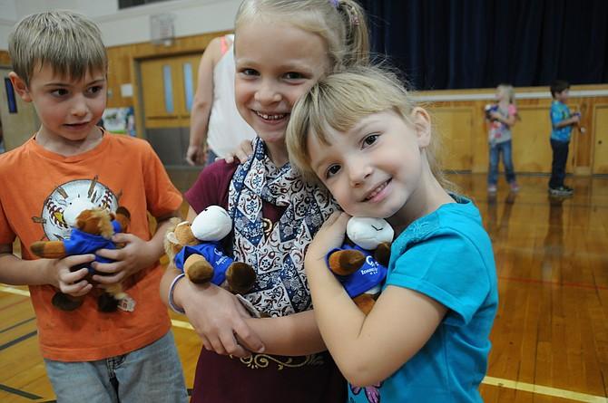 Kindergarten cousins (L-R) Julia Klapprich and Kendal Fogleman hug their new reading buddies while a classmate looks on.