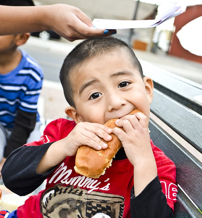 Christopher Marroquin Blanco, 3, of Mabton, chomps down on a hot dog during last night's season finale for the Sunnyside Farmer's Market at Centennial Square.
