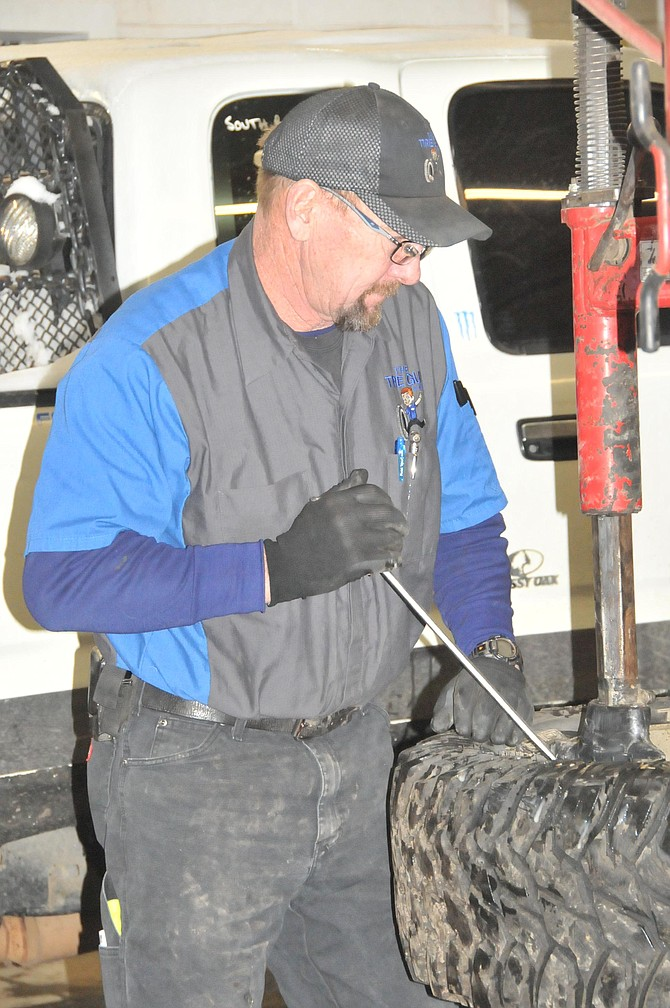 Rick Workman, one of the managers at The Tire Guy in Cottonwood, attempts to remove a tire from its rim.