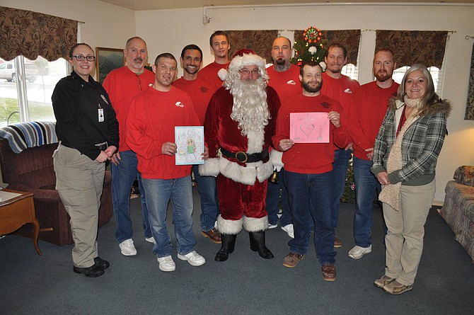 Inmates from North Idaho Correctional Institution at Cottonwood handed out presents of their own making on Friday, Dec. 23, to residents at the Monastery of St. Gertrude, Cottonwood Shelter Home, and in Grangeville at Meadowlark Homes and Grangeville Health and Rehabilitation. The gifts – Christmas stockings and marigold seedlings – were produced by inmates through life skills classes as part of their incarceration programs. Participating inmates were (red shirts, not in order) Adam Faulkner, William Mathers, Everett Linsenmann, Jacob McConnell, Ryan Moore, Randy Melius, Robert Ambs and Shane Whitney. Pictured with inmates at Meadowlark were (L-R) NICI staff Sgt. Lacey Graham, education instructor Emmett Wilson, and volunteer/religious coordinator Gail Gates. Those interested in volunteering to help at NICI can call 962-3276.
