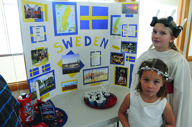 Mari Schwartz, dressed as St. Lucia, is seen here with her little sister in front of the Sweden display she and her twin brother, Jesse, made.