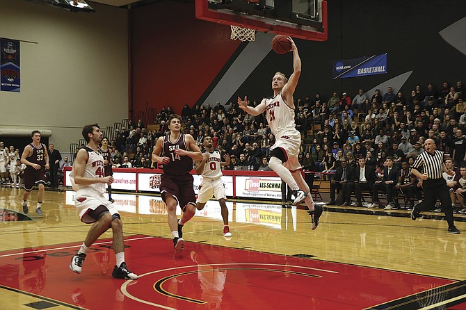 Western Oregon junior Tanner Omlid goes up for a slam dunk against Seattle Pacific on Saturday night. Omlid finished the game with 18 points, 15 rebounds and a school and conference record 11 steals. The Wolves won 84-70 to improve to 13-9 overall and 10-4 in Great Northwest Athletic Conference play.