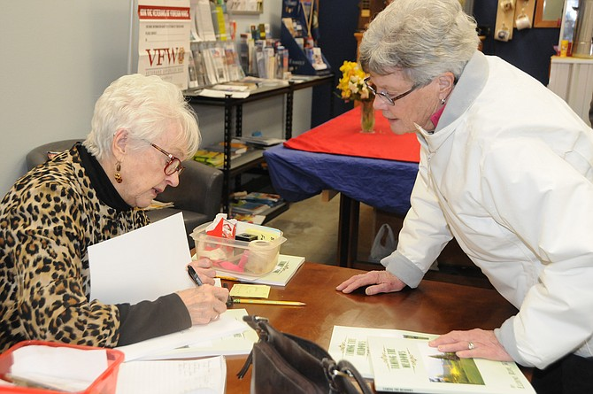 "Eldene Wasem of Grangeville signs a copy of her book, ""Taming the Meadows,"" Thursday Feb. 9, at the veterans center, for MaryAnn Solberg (right). Wasem has sold out of two printings; she will take orders for a third to see if there is enough interest. To be placed on a list call her at 983-0195."