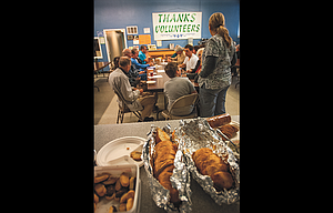 Volunteers with The Dalles Community Meals share dinner prior to their 34th annual business meeting and open house Tuesday evening. On the far wall is a banner thanking volunteers for their work, which is critical to sustain the program that offers free hot meals at the 315 West Third facility.