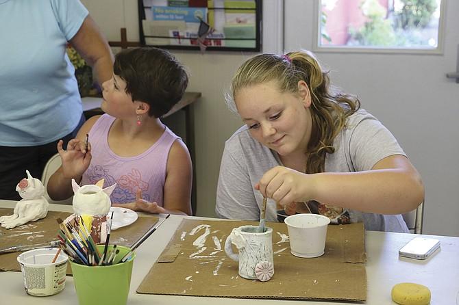 Lileigh Deforest, 9, (left) and Savannah King, 13, paint ceramic mugs at Ash Creek Arts Center summer art camp.
