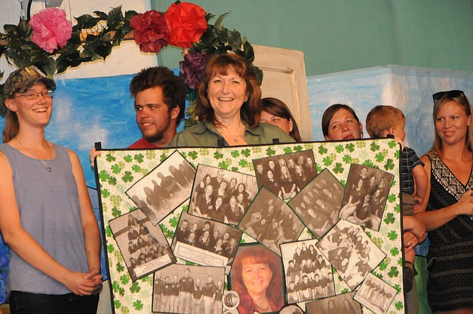 Susie Heckman, Idaho County 4-H Program Director, is surrounded by past 4-H Ambassadors and quilt honoring her and 20 years of the Ambassador program.
