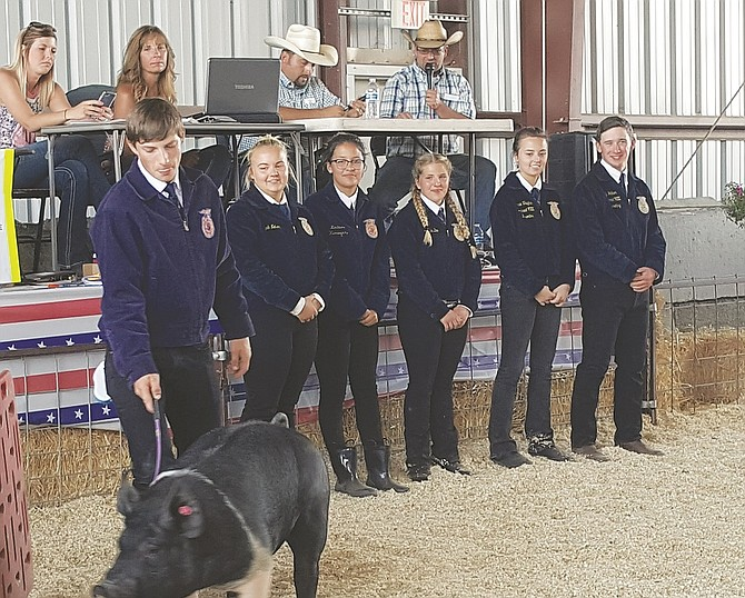 Chandlor Bucklin, left, vice-president of Columbia High's Future Farmers of America chapter, shows the chapter's donated hog last month during the Market Livestock Sale at the Klickitat County Fair. The local chapter showed and sold the hog as a fundraiser for CHS FFA. (Columbia High FFA photo)