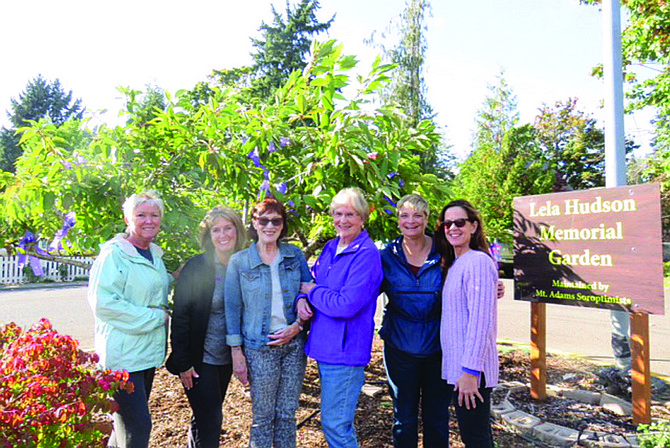 Mt. Adams Soroptimist members hang purple ribbons at the Triangle Garden in White Salmon. The organization is joining with Soroptimists worldwide in providing information about domestic abuse/violence prevention. (Submitted photo)