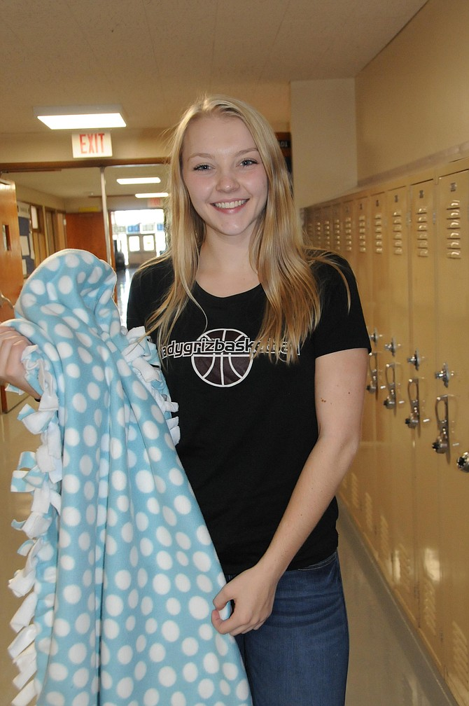 Mikayla Ruzicka shows one of the blankets she made with GHR residents.