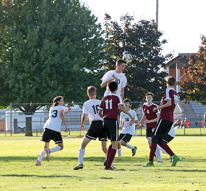 Logan Graber (10) goes up for a header against Crescent Valley on Thursday.