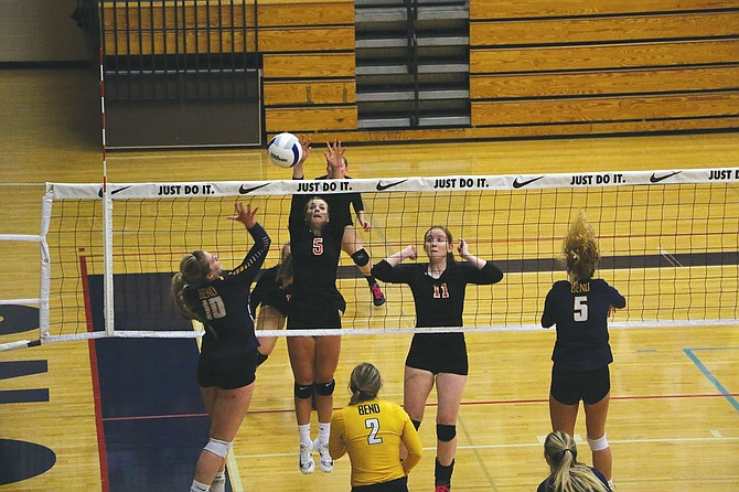 Emma Classen (5) goes up for a block against Bend on Friday afternoon.