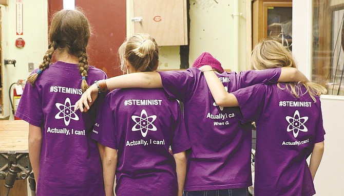 """Fifth-graders Kailey Peterson , Wren Greeley, Genevieve Kingsford-Smith, and Madeline Ayer sport their #STEMinist shirts that they made in the all-girls after-school STEM club. #STEMinists club T-shirts bear the statement of """"Actually, I can!"""" on the back"""