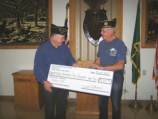 Mt. Adams Elks Lodge representative and American Legion member Rudy Dierickx (right) presents American Legion Post 87 Commander Bill Kupchin with a $1,100 grant. The money will be used by the Legion to support indigent veterans