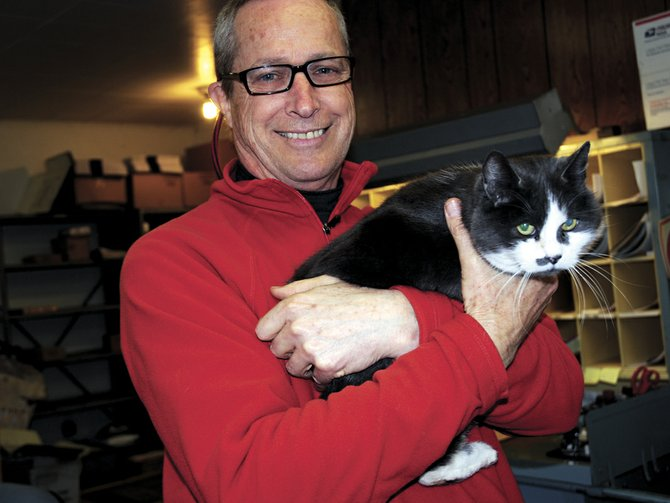 Curly, the Odell post office cat, said goodbye Friday to John Smith, who retired Friday after 19 years as postmaster. 