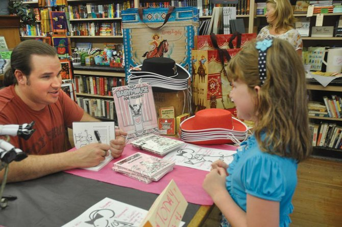 Matthew Holm, left, signs a copy of one of his Babymouse books for fan Alexandria Rector, right, at Klindt's Booksellers in The Dalles Sept. 19. Holm spoke to local students about what it is like to be an author.	Photo by Jade McDowell