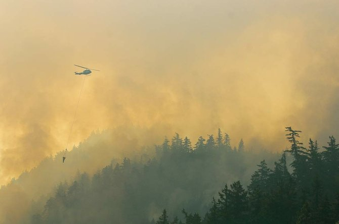A small helicopter arrives to help fight a fire as it climbs up the Oregon side of the Columbia River Gorge just east of Hood River Wednesday morning. Mark B. Gibson photo