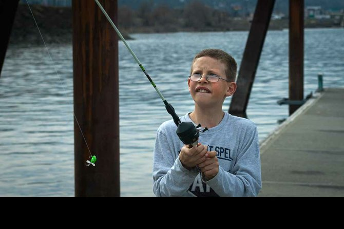 A young boy concentrates on his next cast while fishing at The Dalles Marina. FILE PHOTO Mark B. Gibson