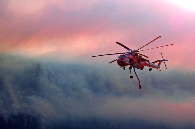 Amazing Helicopter Pilots working valiantly on the Milepost 66 Fire, with the sun setting on the smoke.