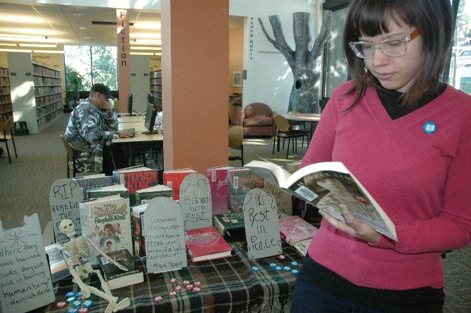 "BANNED BOOK Week: Kathleen Joritz, adult services librarian, peruses Harper Lee's ""To Kill A Mockingbird,"" from the Hood River Library display."
