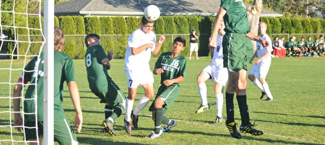 Fabian Muñoz (above) closes his eyes the moment before heading a corner kick into the goal Tuesday afternoon in the Eagles' 2-0 win against Pendleton.
