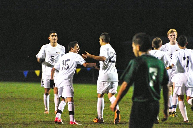 Jaime Frias (20)  of Hood River Valley is congratulated by teammate Brian Manzo after scoring against Rex Putnam in the first round of the state playoffs.