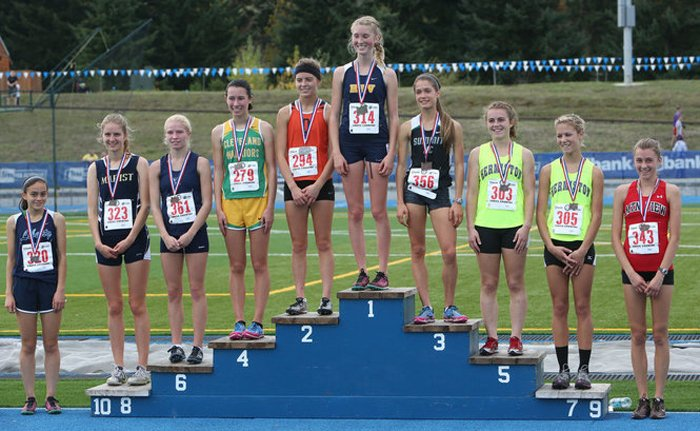 Grace Grim atop the medal stand after winning the 5A state cross country title.