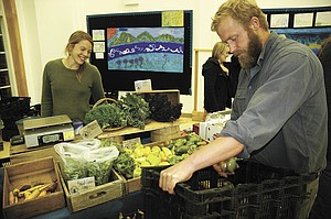 Local bounty keeps coming, even in late fall: Paul Brown and Laurel Bourret of Wildwood Farms in Hood River stock up during Gorge Grown Farmers Market Thursday at Hood River Middle School. The final market will be Nov. 15, and it concludes with the Empty Bowls dinner for FISH.