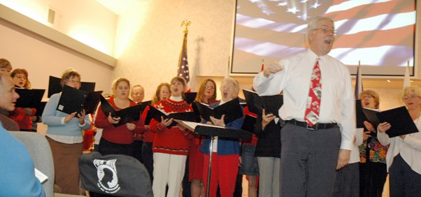 Mid-Columbia Choir, under the direction of Perry Cole, sings a patriotic medley at Anderson's Tribute center. The chair at the front left was left empty to honor POW/MIA's.