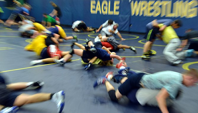 Takedown time: HRV wrestlers watch as juior Andrew DeHart practices a double leg takedown on coach Trent Kroll at practice this week.