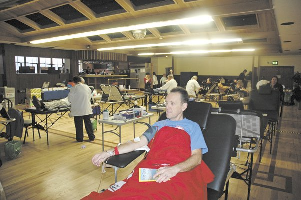 "BLOOD donor Norberto Maahs reads ""Curious Gorge"" as he donates blood Friday at the Hood River Elks Lodge."