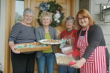 WARMING up their cookie pans, and voices, are Lionesses Sue Guenther, left, Jan Tatyrek, Suze Nigl and Pennie Burns, at Burns' west Hood River home, where the door is adorned with a wreath purchased in support of Soroptimist International.