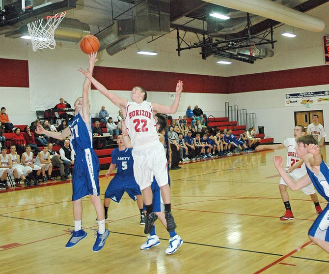 horizon Hawk Ryan Aldrich goes for a rebound against an Amity player.