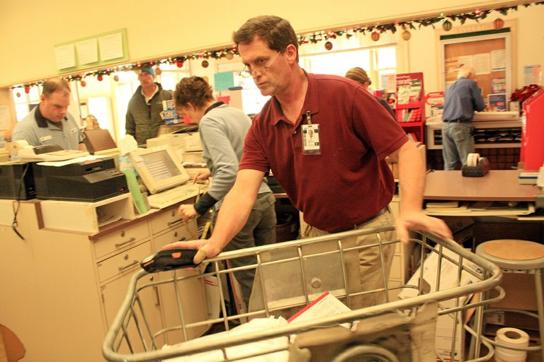 POSTMASTER Kevin Branson sorts parcels and transports while Hood River post office staff handle a busy front counter.