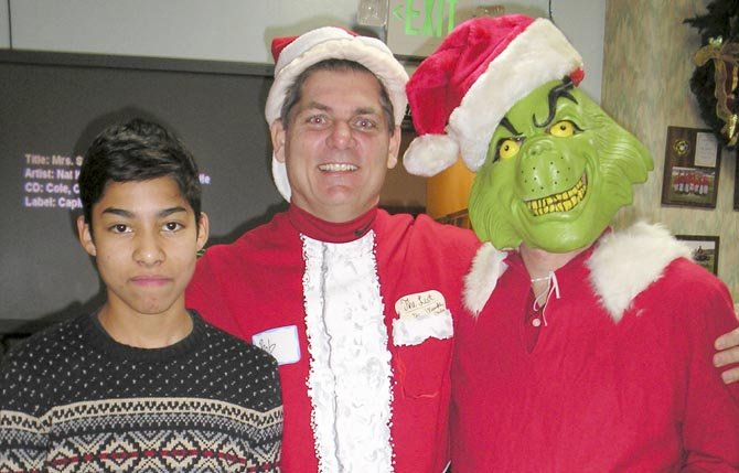 Adal and Big Brother Bob share holiday cheer with the Grinch at the annual Breakfast with Santa for Big Brothers Big Sisters of the Columbia Gorge.	Contributed photo