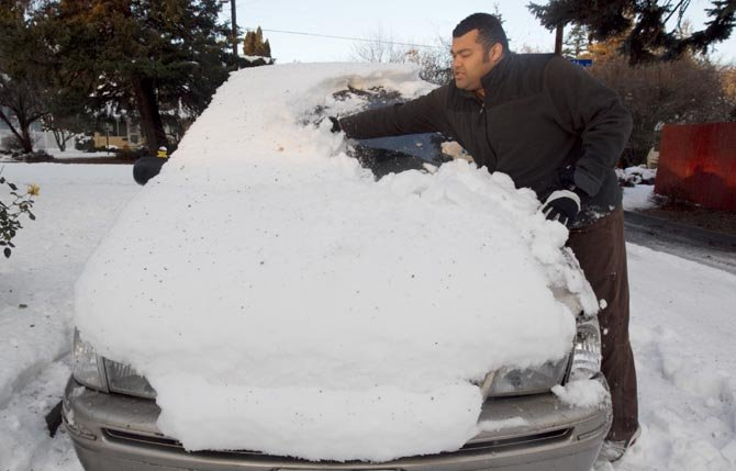 Brice Davis cleans the snow from his car in Yakima, Wash., Dec. 17. 