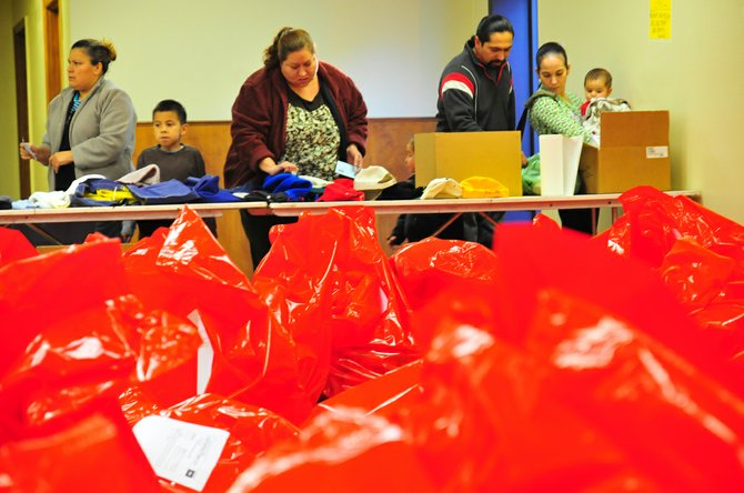 FAMILIES receive their Christmas food and gifts at the 2011 Christmas Project distribution event; details at left.