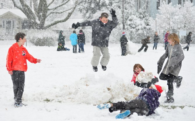 May Street Mayhem: The first snowfall of the winter gave school kids an excuse to party during lunch break Wednesday. Pictured here are students at May Street Elementary School destroying a snowman that another group of students made during their lunch break. 
