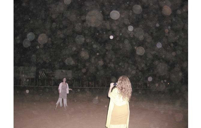 Clyde Sanda took this picture showing thousands of orbs surrounding a woman as she poses for her friend, during his trip to Brazil to see a famous faith healer, John of God. The orbs are not visible to the naked eye, Sanda said, but appear in pictures.   	Contributed photo