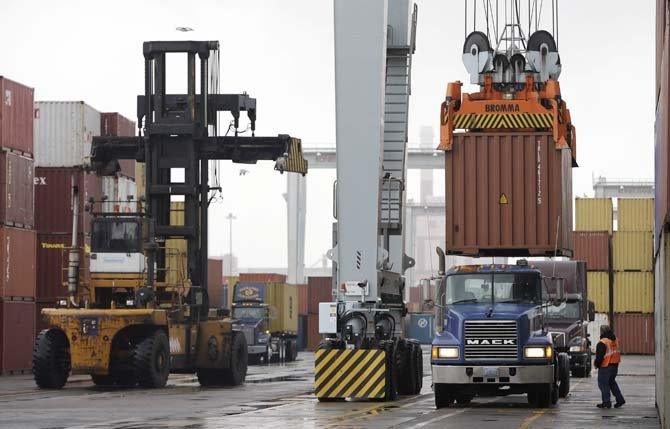 a truck driver watches as a freight container, right, is lowered onto a tractor trailer by a container crane at the Port of Boston in Boston Dec. 18. The longshoremen's union may strike if they are unable to reach an agreement on their contract, which expires Dec. 29, 2012. 	AP Photo/Steven Senne, File