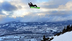 Never a dull day: Conditions were right Thursday for this rare treat on the east hills of the Hood River Valley. Pictured here is Gorge resident Todd Anderson soaring over the hillside with a snow-covered central valley as the backdrop.