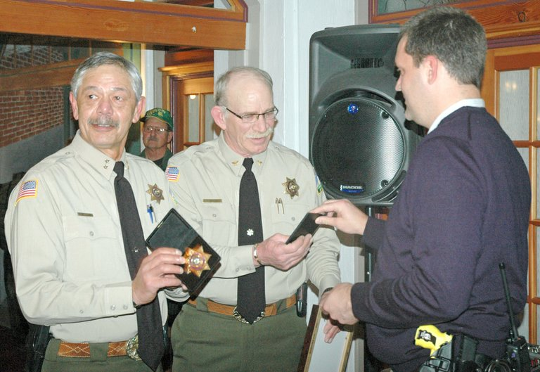 SHERIFF Joe Wampler, left, and Chief Deputy Jerry Brown admire their retiree badges, presented Thursday by Sheriff-elect Matt English in Thursday's standing-room-only reception at Hood River Hotel. Wampler and Brown will both serve as reserve deputies after retiring in January.
