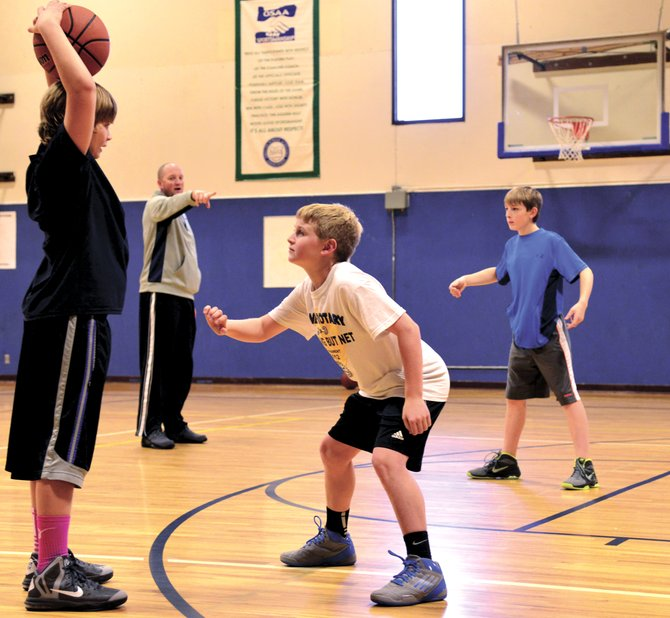Practice, practice, practice: Hood River Eagles seventh-grade traveling baskeball team practices Thursday to get ready for the first tournament of the winter season this weekend. Pictured is coach Devon Wells giving defense instruction to players (from left) Luke Harter, JJ Mears and Trenton Hough.  The group is one of five youth traveling teams from Hood River.  