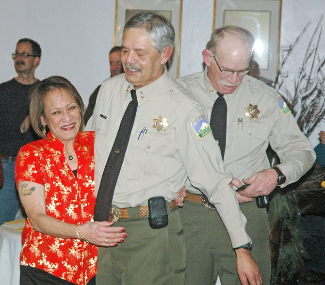 Sheriff Joe Wampler hugs his wife, Charmaine, at Thursday's retirement reception for Wampler and Chief Deputy Jerry Brown, right.